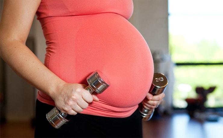 schwangere Frau hebt Gewichte